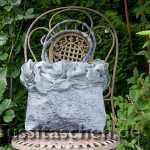 Handtasche aus grauem Jaquard mit Tüllrand und Perlen bestickt. Innenfutter magenta. 298,-€.