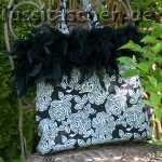 Handtasche aus schwarz-weißem Rosenstoff mit schwarzem Federrand. Innenfutter schwarz mit weißen Pünktchen. Verkauft.
