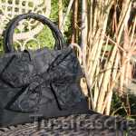 Handtasche aus schwarzer Dupionseide mit bestickter Wechsel-Schleife und Swarowski-Steinen. Innenfutter schwarz-weiß-gepunktet. Verkauft.