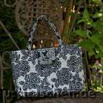 Handtasche aus weiß-schwarzer Rosenstoff mit Rosenverzierung. Innenfutter schwarz mit weiss-silbernen Pünktchen. 198,-€