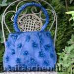 Handtasche aus nachtblauer Seide in Tüll verpackt, mit Puscheln und Swarovski-Steinen bestickt. Innenfutter graue Seide mit blauer Blütenstickerei. Verkauft.