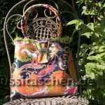 Handtasche aus orangebuntem Rips mit Paisleymuster und grünem Puschelrand. Innenfutter orange. 238,-€