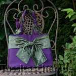 Handtasche aus violettem Stoff mit leichtem Glanz und olivgrüner mit Sternen bestickter großer Schleife. Innenfutter olivgrün. 298.- €