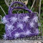 Handtasche aus violettem Stoff mit fliederfarbener Borte und fliederfarbenen Puscheln. Innenfutter fliederfarben. 218.- €
