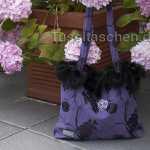 Handtasche aus violettem Rosenstoff mit Pelzrand